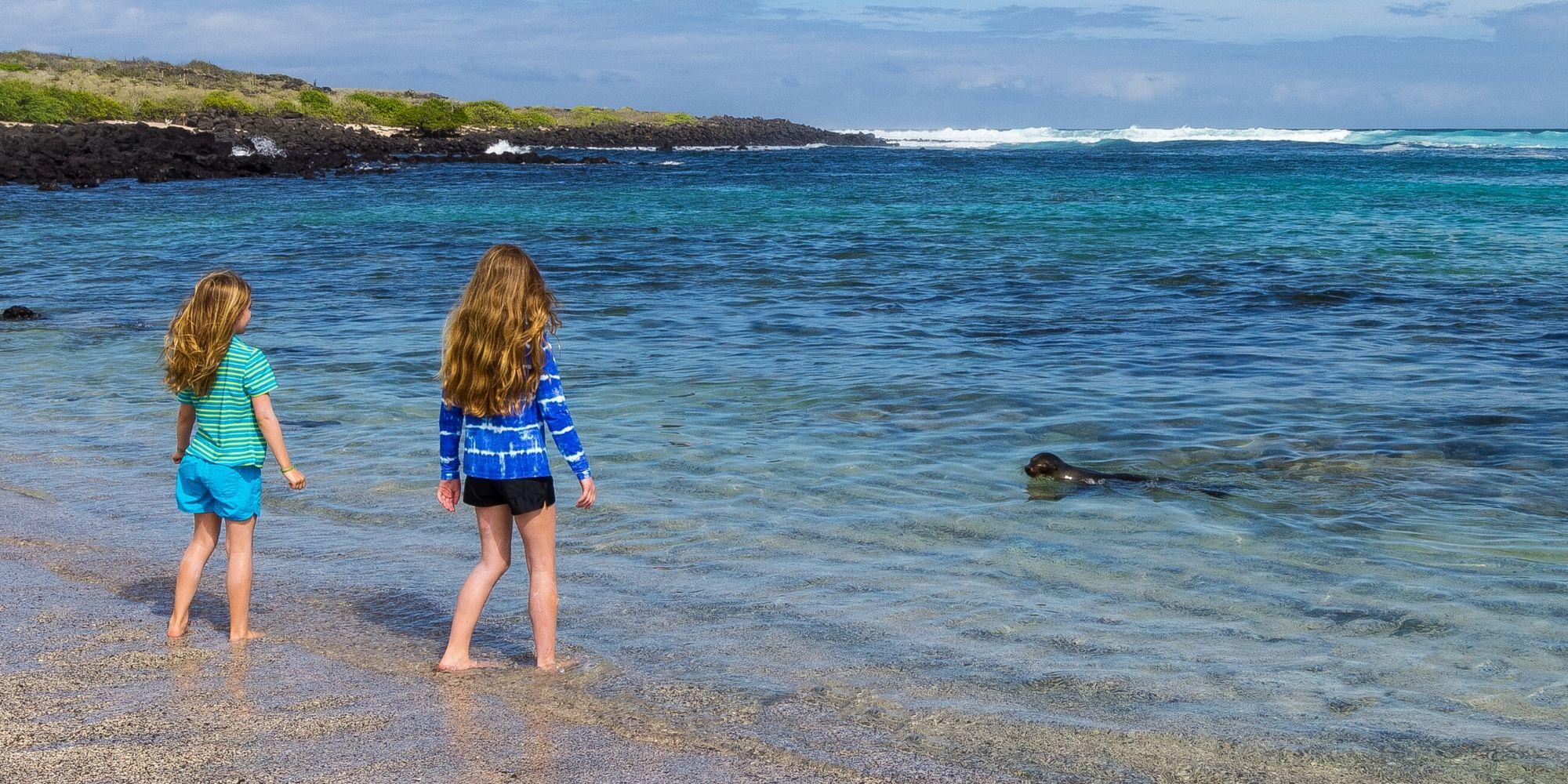 Kids on Galapagos beach with Sea Lion
